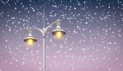 Luminous street lantern with snowflakes background.