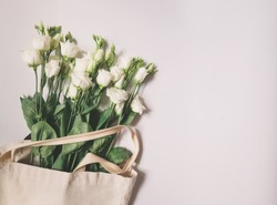 luminous white Lisianthus flower bouquet laying in a linen eco bag, horisontal flower background template