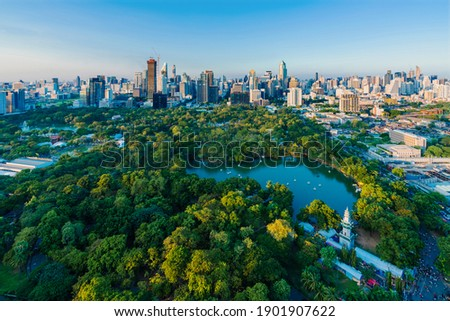 Lumpini Park and Bangkok city the morning , With flare of sunlight effect create reflection at the building.