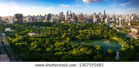 Lumpini park in center of Bangkok city in day time with Building and blue sky background, Bangkok, Thailand