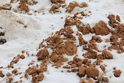 Lumps of loose brown soil and clay covered with snow