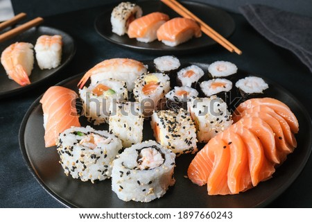 Lunch at the sushi bar. Set of sushi and rolls unagi maki on a black plate on dark background top view. Sushi Delivery to Home Order Online. Takeout coronavirus food.