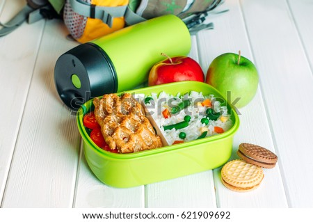 Lunch box filled with rice and sandwich near thermos, fresh apples and biscuits in front of kids school backpack on white wooden background ; selective focus