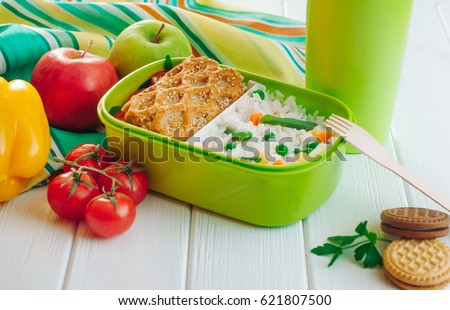 Lunch box filled with rice and sandwich on white wooden background near fresh vegetables and biscuits; selective focus