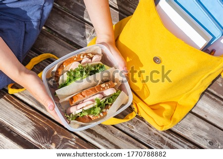 Lunch box in the hands of a child. Sandwiches with bread, lettuce, cucumber and sausages in a plastic container. Snack, school breakfast, lunch. Back to school. Lunch break. Yellow backpack with books
