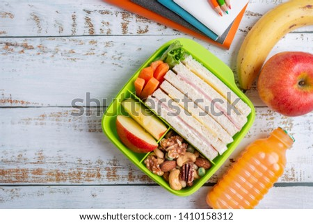 Lunch box set of Ham cheese sandwich with carrot and mixed nuts, apple in box, banana and apple with orange juice. Kid bento pack for school. Top view and Copy space.