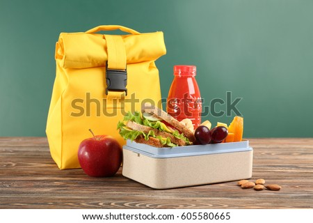 Lunch box with appetizing food and bag on wooden table against chalkboard background