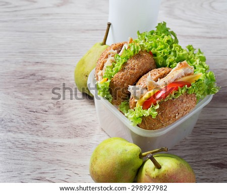Lunch box with burgers, pears and yogurt. Selective focus