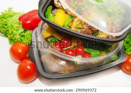 Lunch box with Chinese food and vegetables