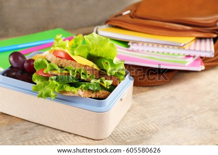 Lunch box with delicious food and stationery on wooden background