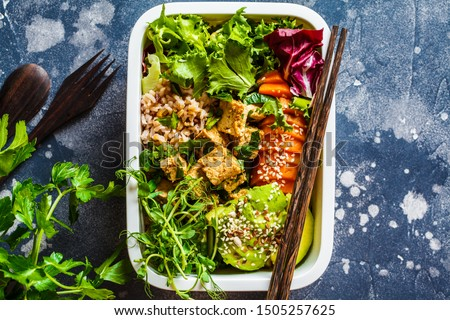 Lunch box with healthy vegan food. Bento box with rice, tofu and vegetables, dark background.