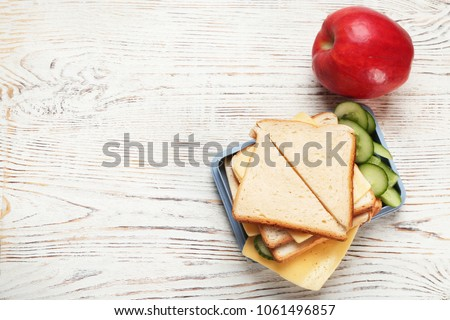 Lunch box with tasty sandwich on wooden table