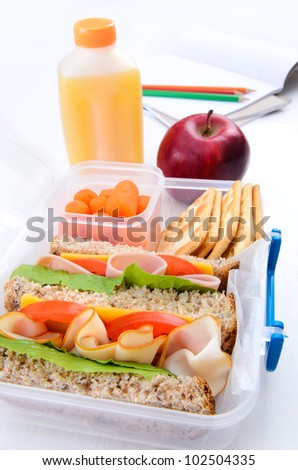 Lunch box with turkey and ham sandwich, crackers, baby carrots, apple and orange juice