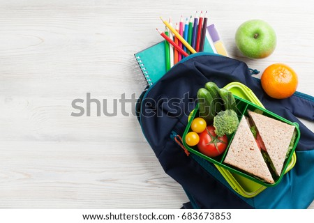 Lunch box with vegetables and sandwich on wooden table. Kids take away food box and school backpack. Top view with copy space
