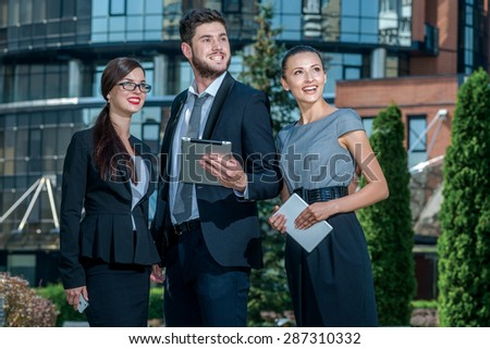 Lunch break. Three successful business people in formal clothes standing on the street to discuss business and keep computers in their hands. Young businessman smiling and looking at the camera