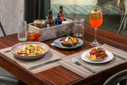 lunch for two: seafood pasta, meat appetizer with egg and julienne in the pan on a wooden table outside at a restaurant with drinks