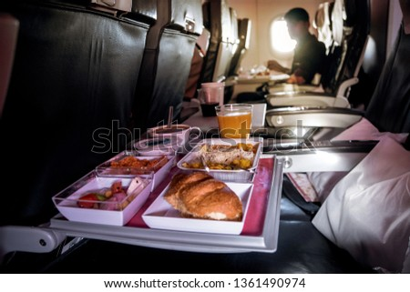 Lunch in airplane. Inflight economy class meal on tray: butter, bread, chicken salad. Fruits: watermelon, pineapple and gold kiwi. Hot dish: rice with vegetables and beef. on-Board meals during ストックフォト ©