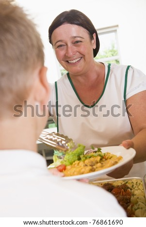 Lunch lady serving salad to student