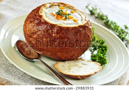 Lunch of soup served in baked round bread bowl