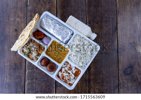 Lunch pack in Indian restaurants with roti subji dal rice sweet and pickle papad and butter milk North Indian Lunch Pack top view selective focus wooden background vegetarian packed food