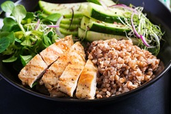 Lunch salad. Buddha bowl with buckwheat porridge, grilled chicken fillet, corn salad, microgreens and daikon. Healthy food.