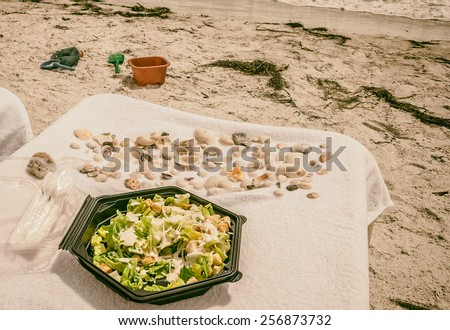 stock-photo-lunch-time-on-the-beach-caesar-salad-in-plastic-box-caesar-salad-with-chicken-served-on-luxury-256873732.jpg