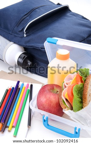 Lunchbox with ham sandwich, apple and oj with schoolbag and water bottle