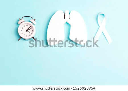 Lung cancer awareness background with white ribbon, alarm clock and lungs on blue. Copy space for text. November lung cancer awareness month.