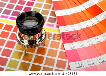 Lupe and a color guide on printed color chart (red, orange and yellow)