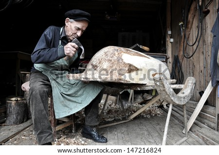 LUPENI - APRIL 20: An unidentified cooper making a traditional wooden vat. Such type of craftmanship are in the way of disappearing in Transylvania. On April  20, 2012 in Lupeni, Romania