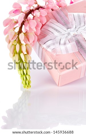 Lupine and gift box. Festive surprise. Box with a bow. Elegant gift. Gift box and lupine flowers.