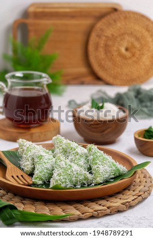 Lupis is a traditional food from Indonesia, made of glutinous rice. It can be sweetened further with shredded coconut topped with a thick palm sugar syrup. Selective focus. Blurry background. Zdjęcia stock ©