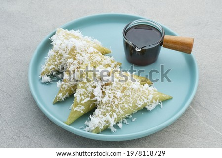 Lupis or Lopis, a traditional Indonesian food made from sticky rice and wrapped in banana leaves. Served with grated coconut and liquid brown sugar. Selective focus image. Zdjęcia stock ©