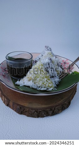 Lupis or Lopis is a traditional Indonesian snack made of sticky glutinous rice, wrapped in banana leaf, shape triangle served with palm sugar syrup and grated coconut                              Zdjęcia stock ©