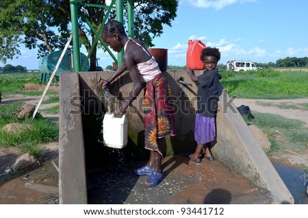 LUSAKA,ZAMBIA–DECEMBER 3:Unidentified African children fetch water many miles away from home and do not attend school to help their family,on December 3,2011  in Lusaka,Zambia