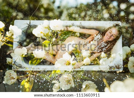 Lush flowering in the garden. Lush cherry blossoms cover the naked body of a smiling young girl, gracefully lying in the bath in the garden.