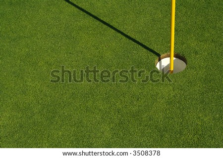 Lush, freshly mowed golf green, flag and cup. Plenty of room for text on the left side. Large enough to isolate either the grass or the cup and flag.