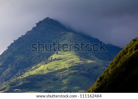 Lush green Andean mountain landscape and rain clouds
