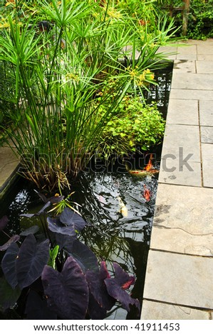 Lush green garden with stone landscaping and koi pond