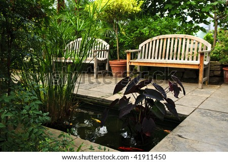 Lush green garden with stone landscaping, koi pond and benches