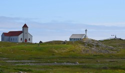 lush green island landscape with church and monument on Ile aux Marin St Pierre and Miquelon