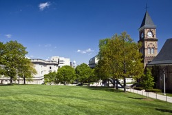 Lush green lawn and trees at the UW campus in Madison, Wisconsin, contrasts with the state capitol building in the distance.