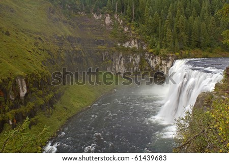Lush green moss thrives as soft mist from spray of roaring Upper Mesa Falls on Henrys Fork of Snake River in eastern Idaho maintains constant moistness on volcanic soil.