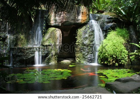 Lush green tropical Koi pond with waterfall from each side.
