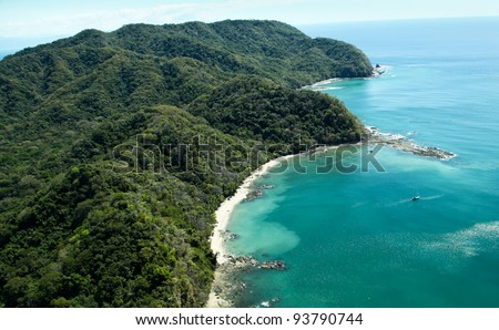 Lush jungle covered mountains stretch out into the Gulf of Nicoya next to the rocky and sandy beach of Ballena Bay in Costa Rica. - stock photo