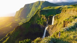 Lush paradise views over green valley, dramatic cliffs and cascading waterfall at Flores Island, The Azores, Portugal