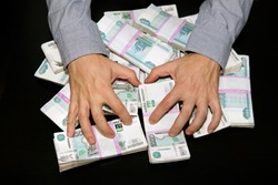 Lust for money. Large stack of banknotes, Russian rubles, banknotes 1000 rubles. hands are grabbing money.