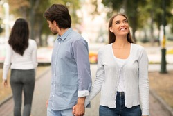 Lustful Cheating Boyfriend Looking At Other Woman Walking With Girlfriend In Park Outdoors. Selective Focus