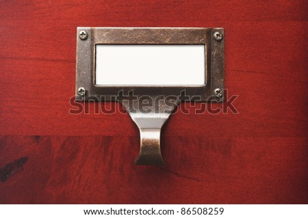 Lustrous Wooden Cabinet with Blank File Label in Dramatic LIght.
