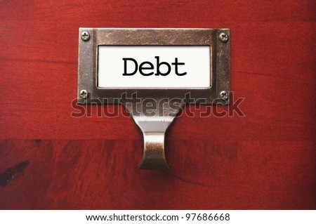 Lustrous Wooden Cabinet with Debt File Label in Dramatic LIght.